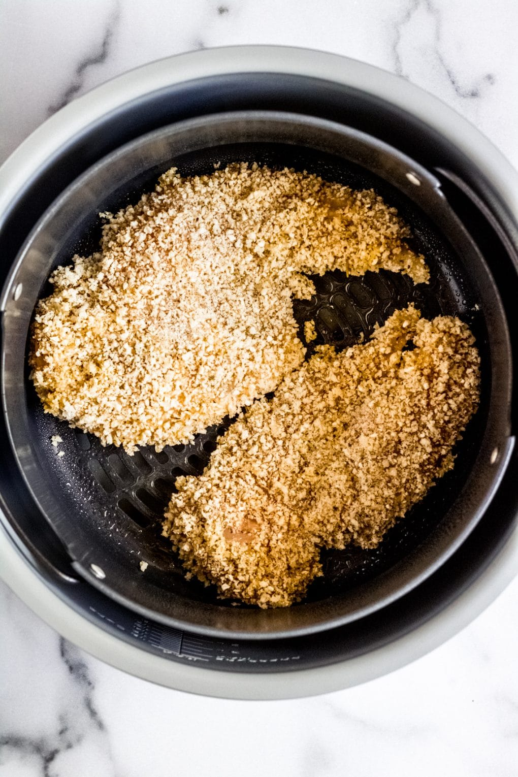two breaded chicken breasts in an air fryer basket