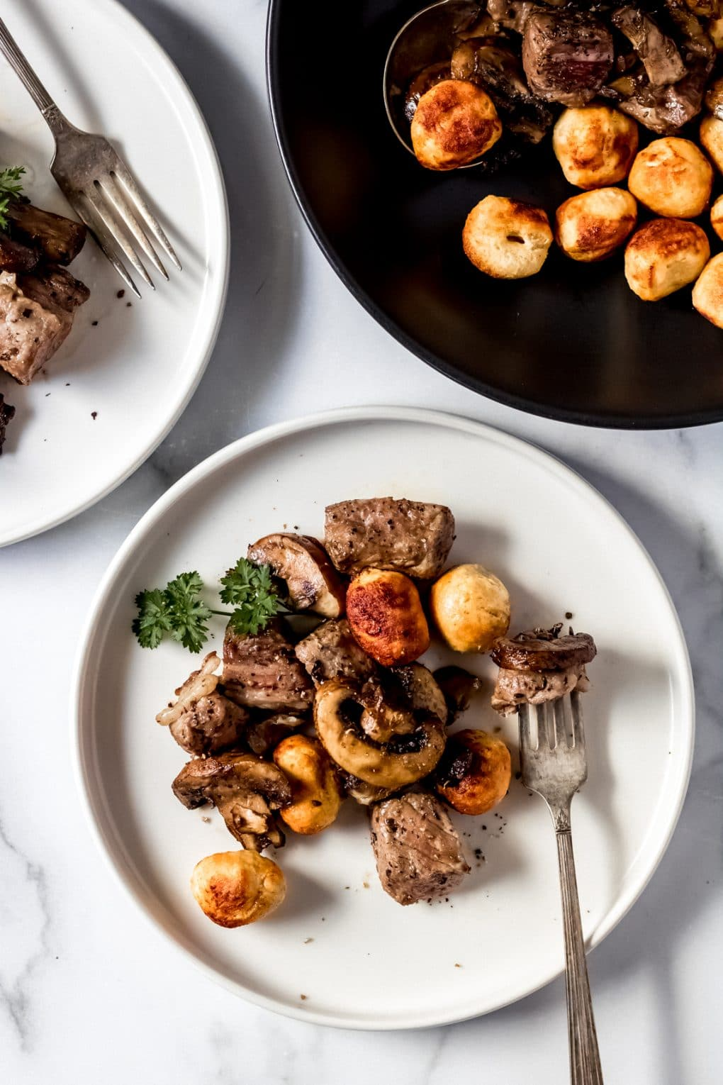 a white plate with gnocchi and mushroom & steak bites on it with a fork.