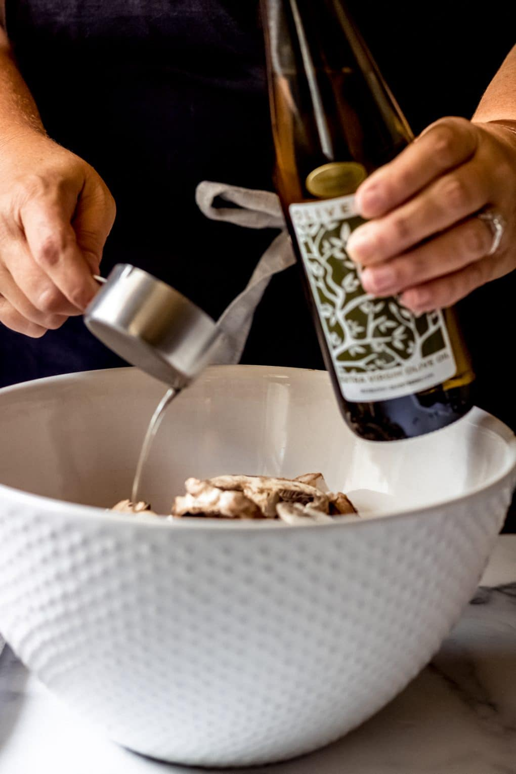 a woman pouring mushroom garlic olive oil into a large bowl