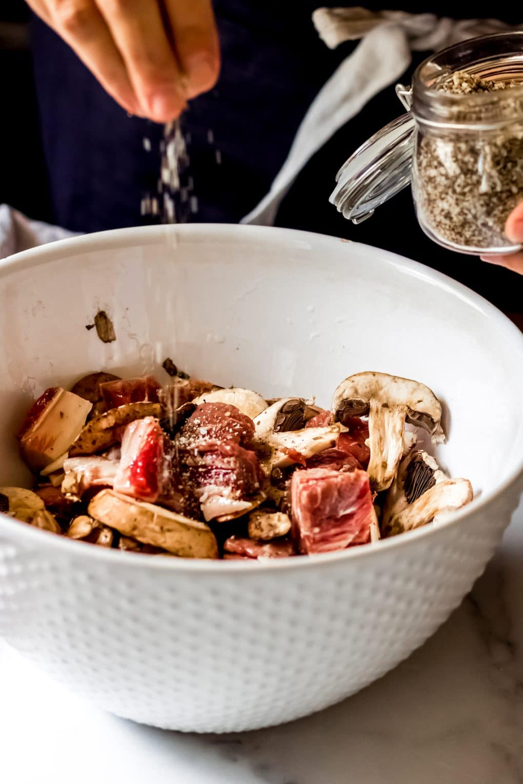a woman seasoning raw steak and mushrooms with santa maria seasoning