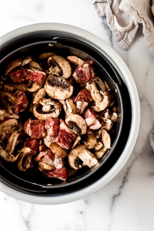 mushroom and steak bites in an air fryer basket