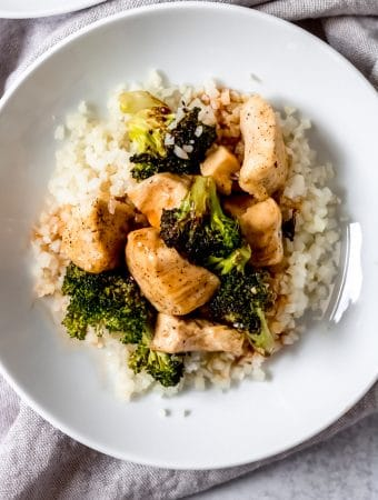 air fryer sweet & sour chicken served over cauliflower rice in a white bowl