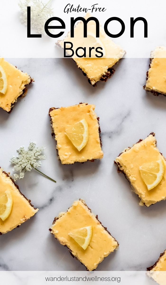 gluten-free lemon bars on a marble top - there's a white flower laying next to the bars