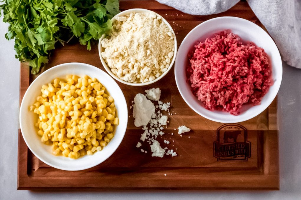some ingredients needed for Mexican street corn beef casserole - a bowl of ground beef, a bowl of corn, a bowl of cornmeal, cilantro, and cotija cheese