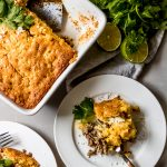 a white casserole dish with mexican street corn beef casserole and two servings dished out onto white plates