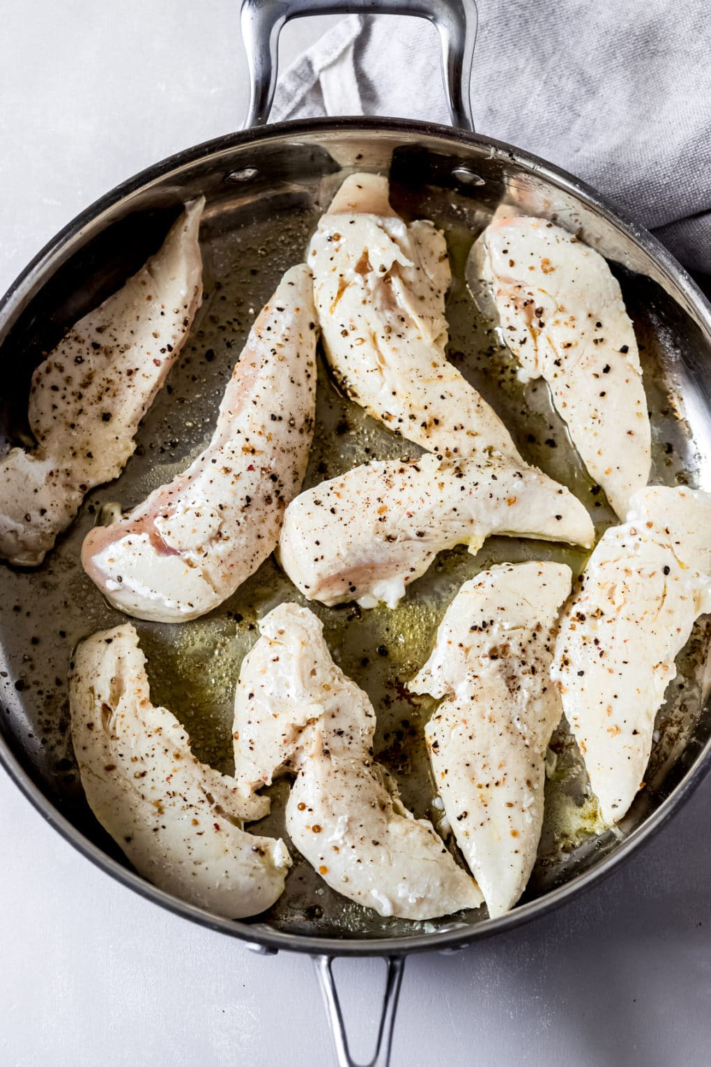 chicken tenders cooking in a stainless steel skillet