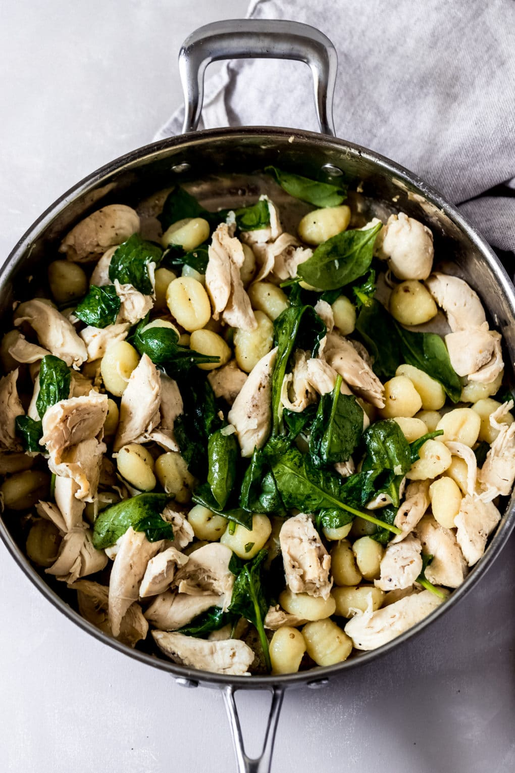 chicken tenders, spinach and gnocchi cooking in a skillet