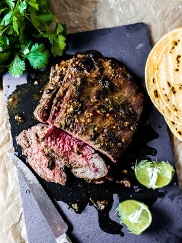 air fryer carne asada on a slate cutting board. There are lime halves, fresh cilantro, and corn tortillas laying nearby