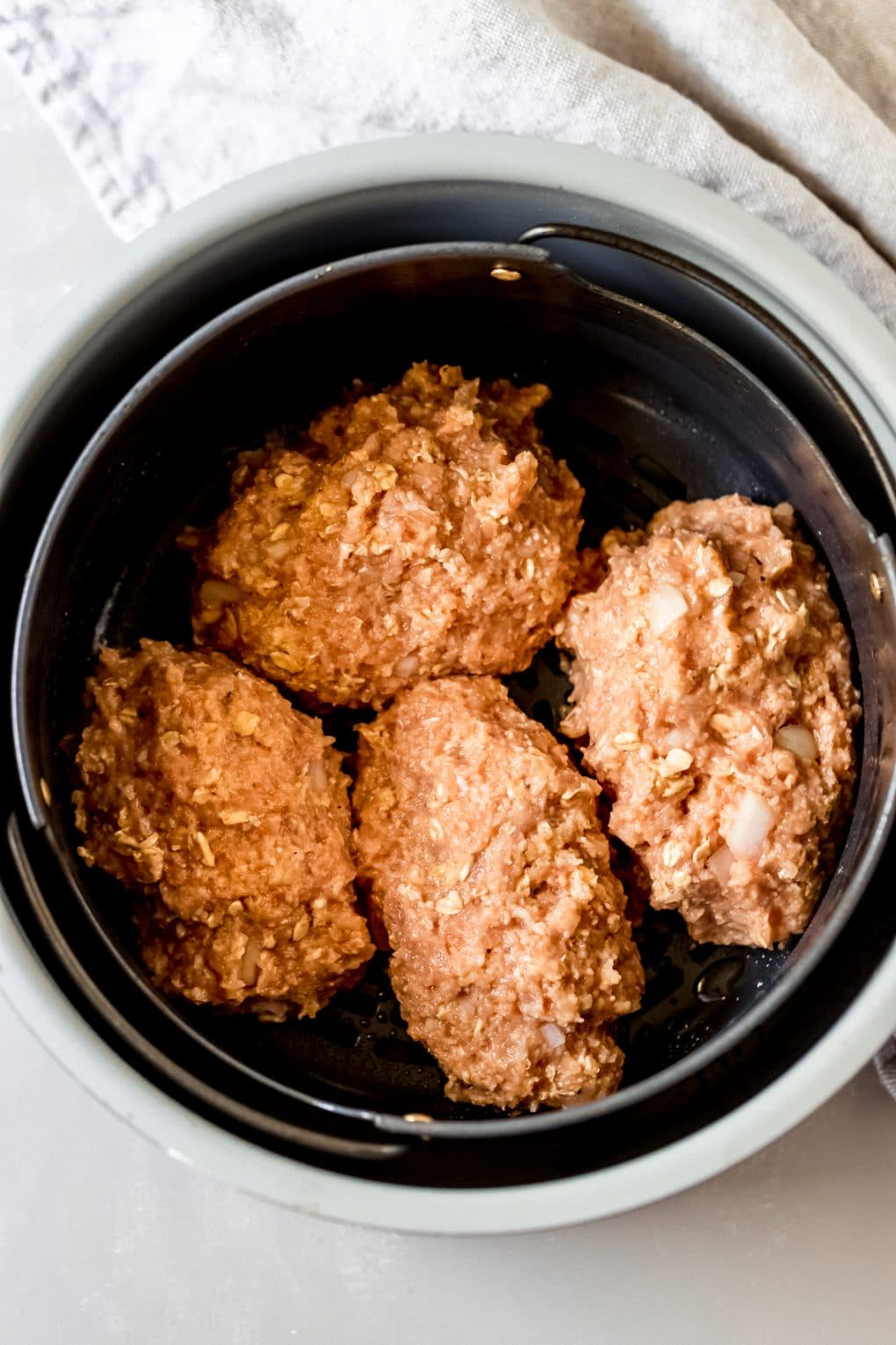 4 uncooked mini chicken meatloaves in an air fryer basket