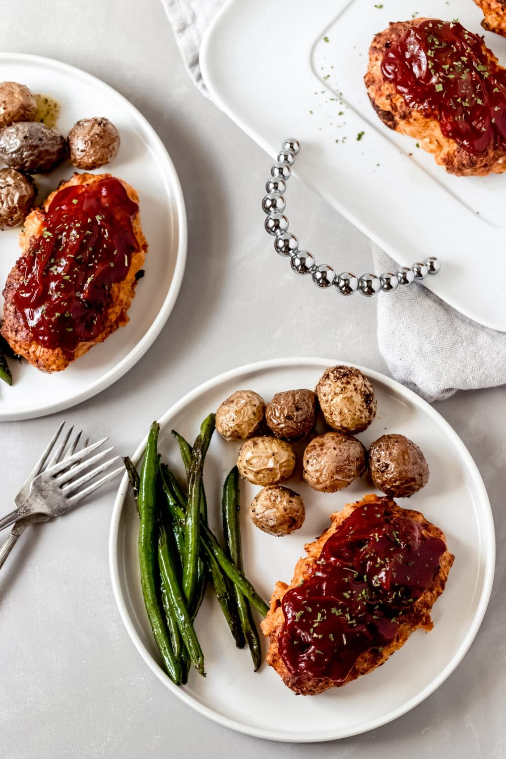 mini chicken meatloaf on a white plate with green beans and roasted potaotes