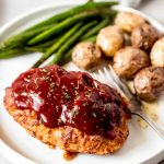a mini chicken meatloaf on a white plate with green beans and potatoes