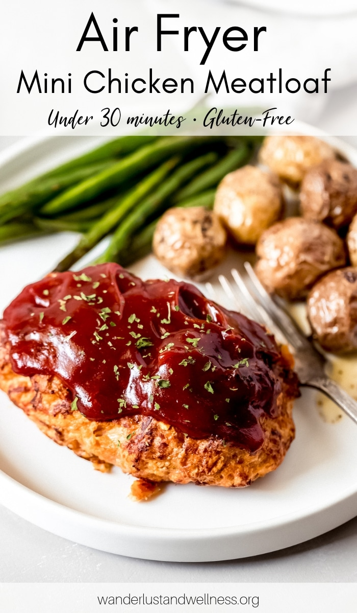 a mini chicken meatloaf on a white plate with a side of green beans and roasted potatoes
