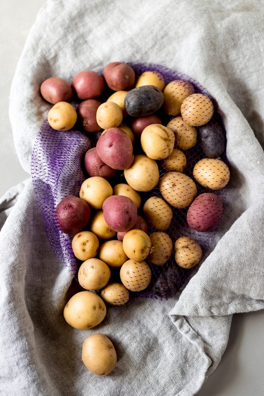 uncooked baby potatoes on a linen towel