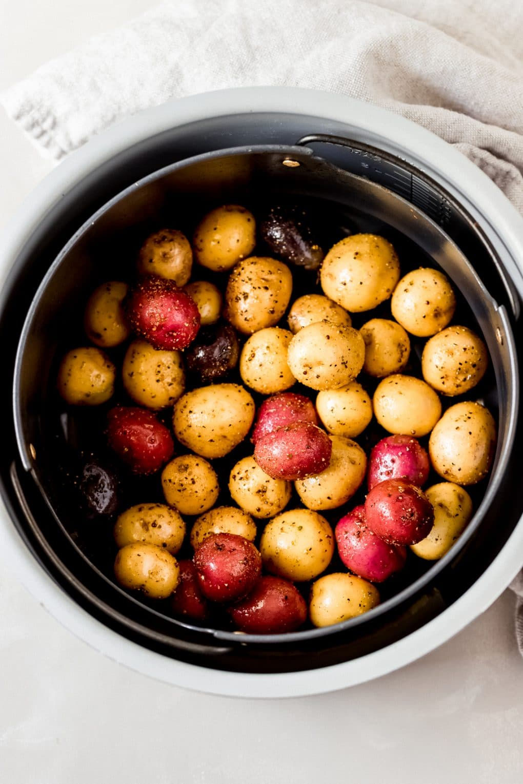 oiled baby potatoes in an air fryer basket