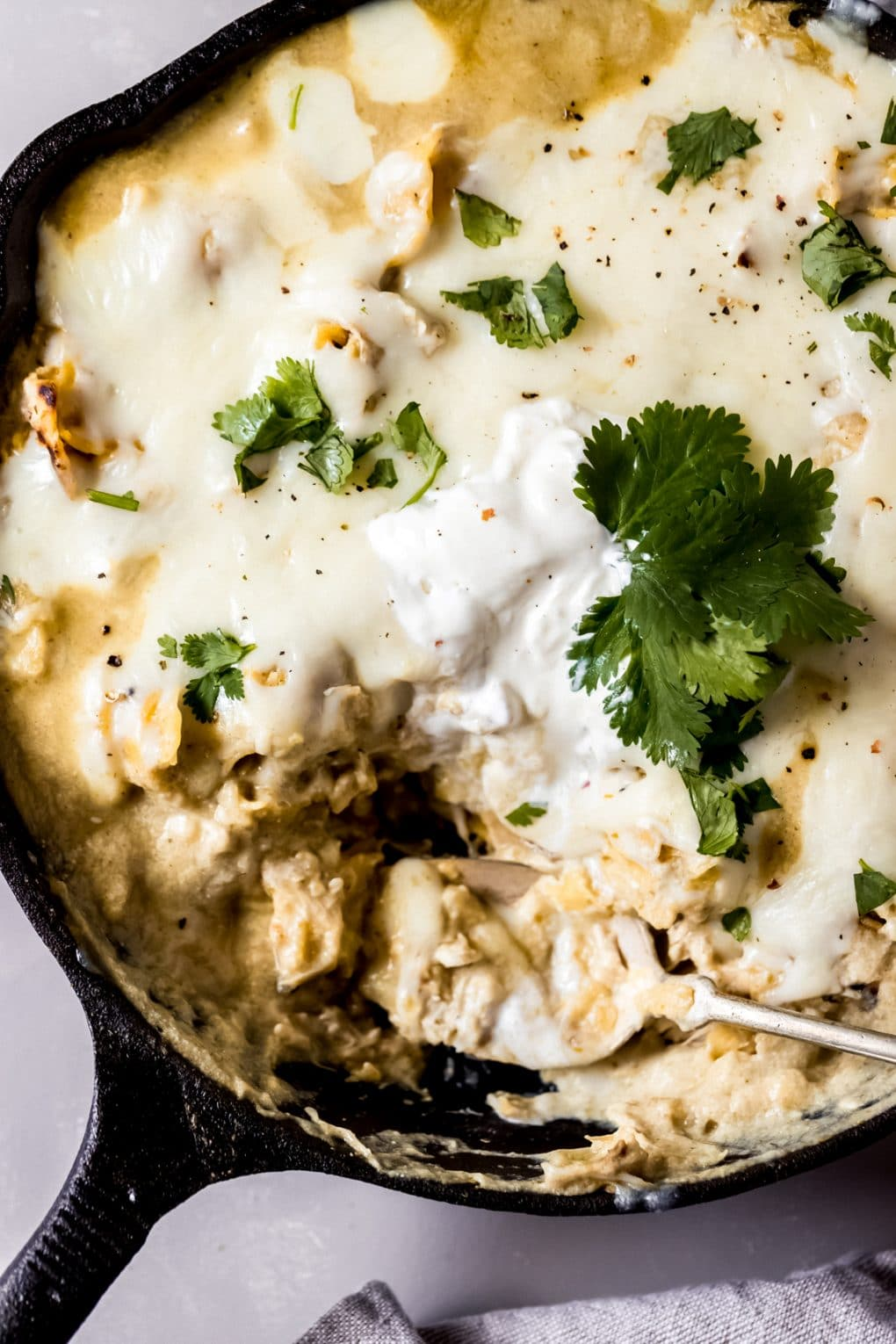 green chicken enchilada skillet in a cast iron skillet with one serving scooped out