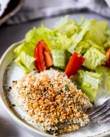 a parmesan crusted cod fillet on a white plate with a side salad