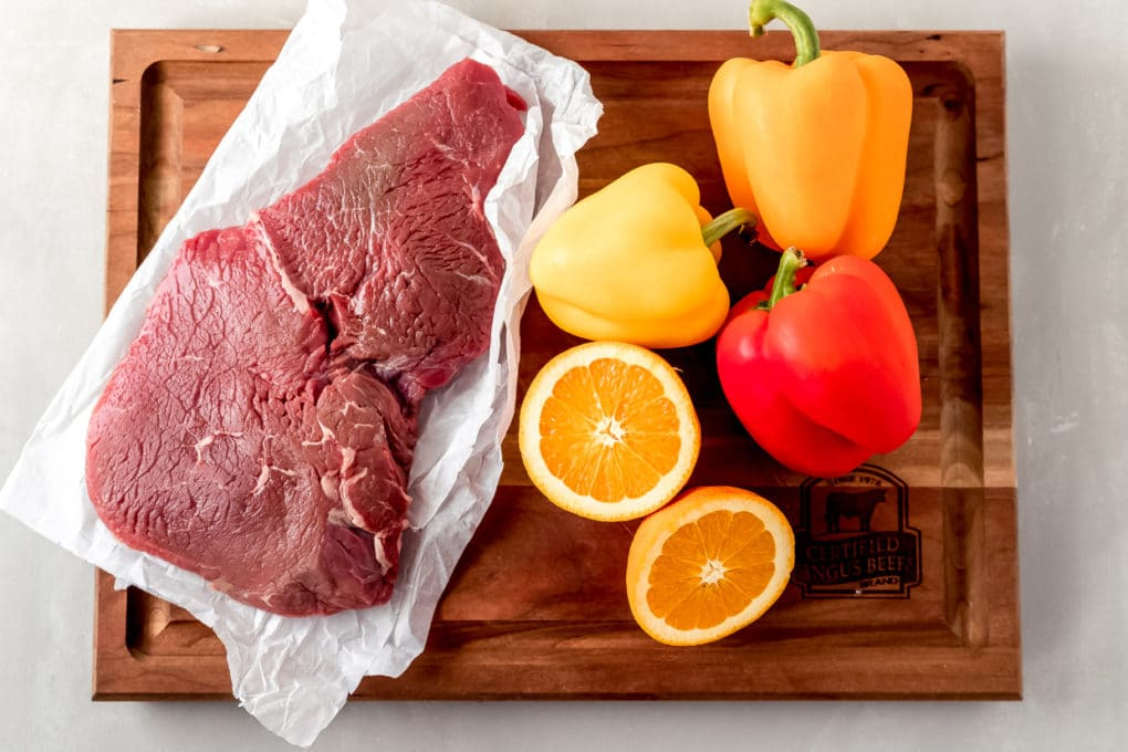 a raw sirloin steak, sliced orange, red, yellow and orange pepper on a wooden cutting board