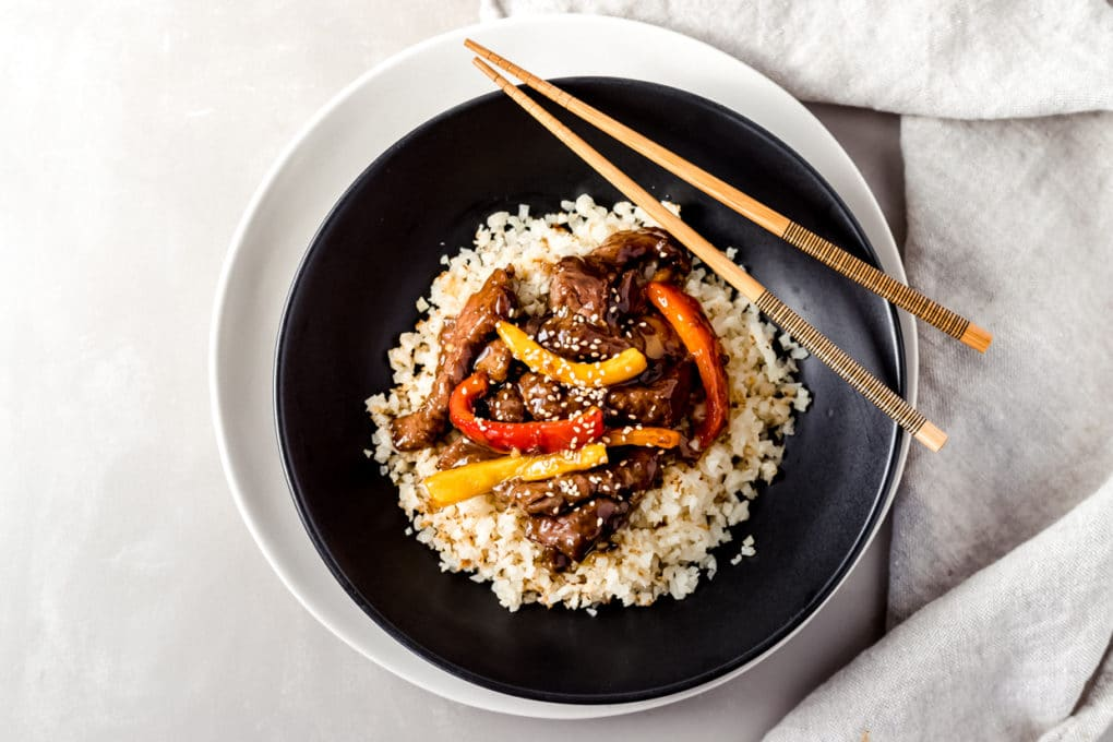air fryer orange beef in a black bowl that's sitting on a white plate with chopsticks laying across the top of the bowl
