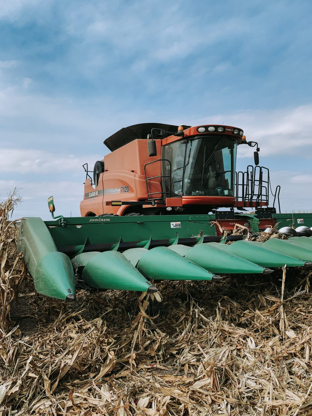 a picture of a farming combine in a corn field