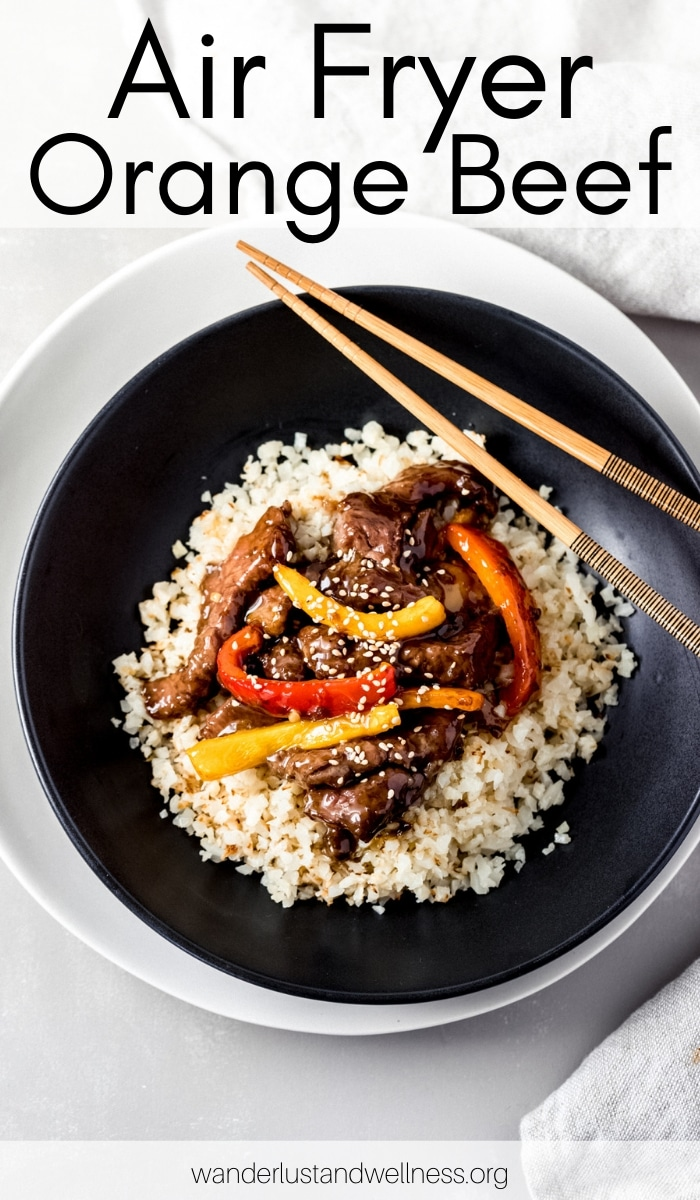 a black bowl with air fryer orange beef inside. there are chopsticks laying across the bowl