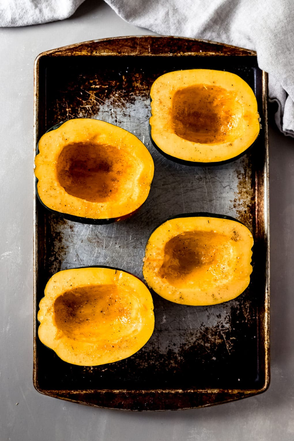 two acorn squash cut in half and laying on a baking sheet ready to bake