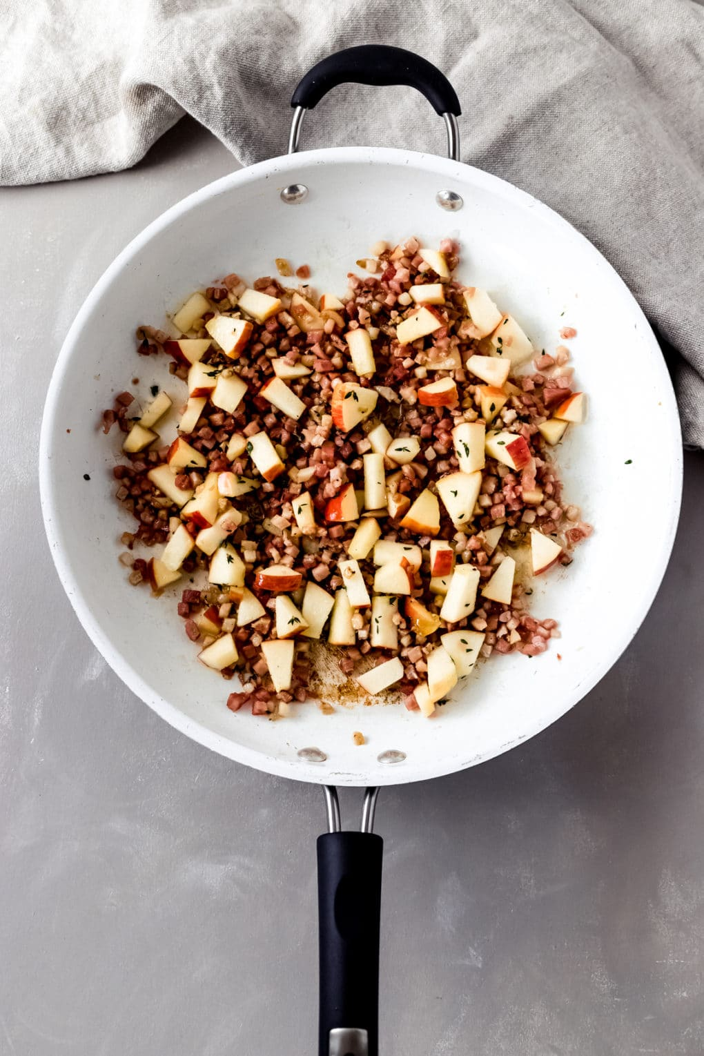pancetta, apples, and thyme cooking in a skillet
