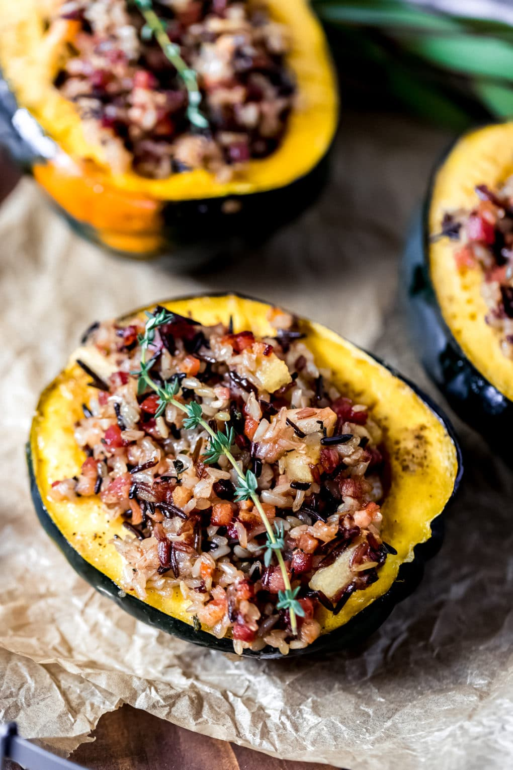 stuffed acorn squash on parchment paper on a wooden serving tray