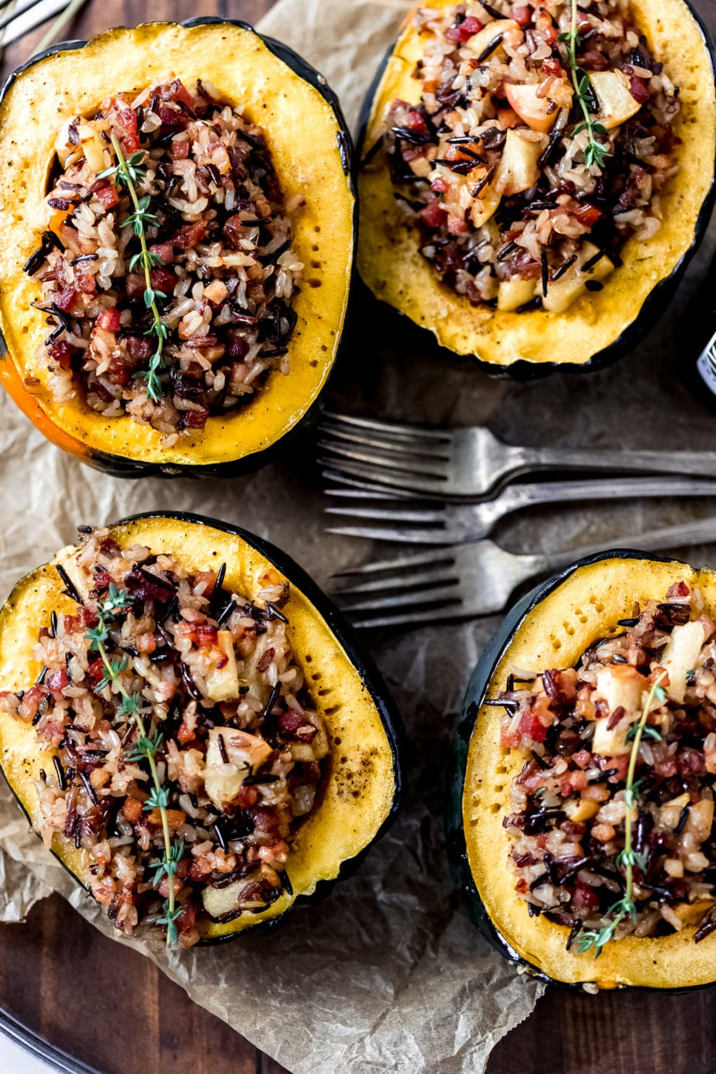 four stuffed acorn squash on a wooden serving try with four vintage forks