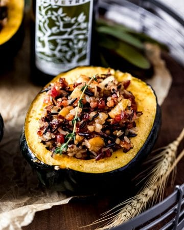 a stuffed acorn squash on a wooden serving tray with a bottle of rosemary olive oil in the background