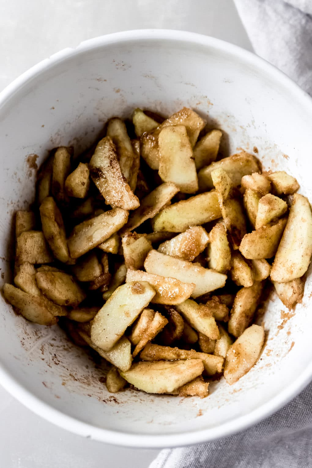 raw apples in a large mixing bowl mixed with cinnamon, sugar, and spices