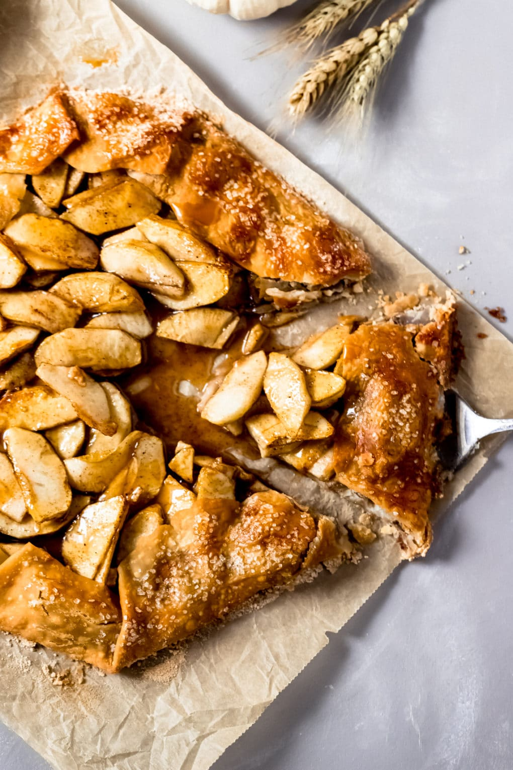 a baked caramel apple galette with one slice cut out