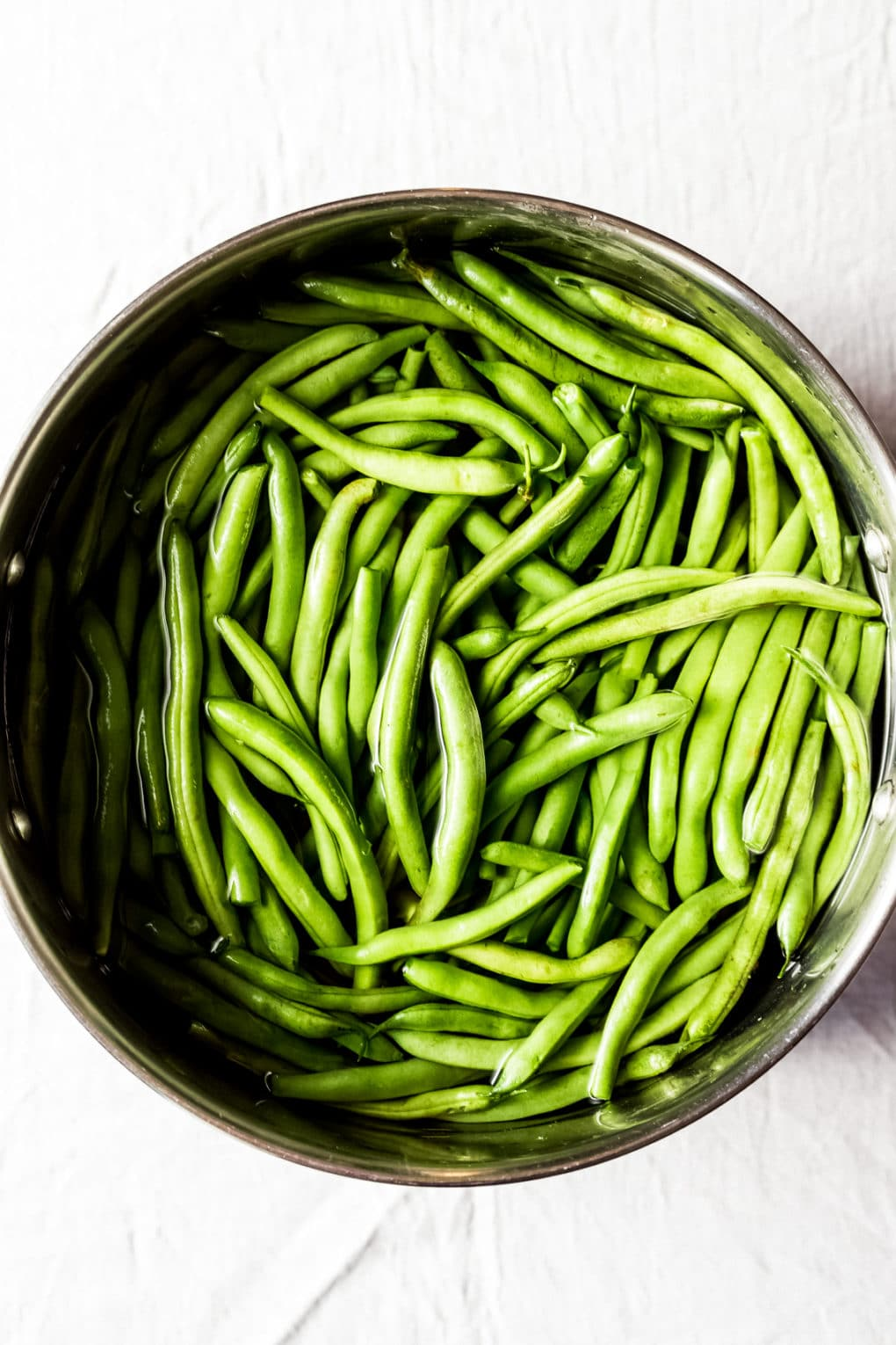 a stock pot of green beans in water