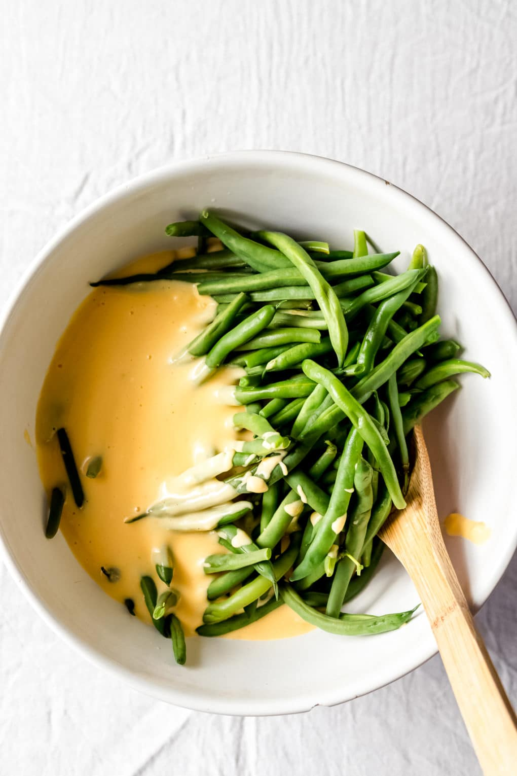 cooked green beans in a white bowl with a yellow cheese sauce and a wooden spoon
