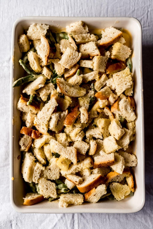 an unbaked casserole dish of cheesy green bean casserole