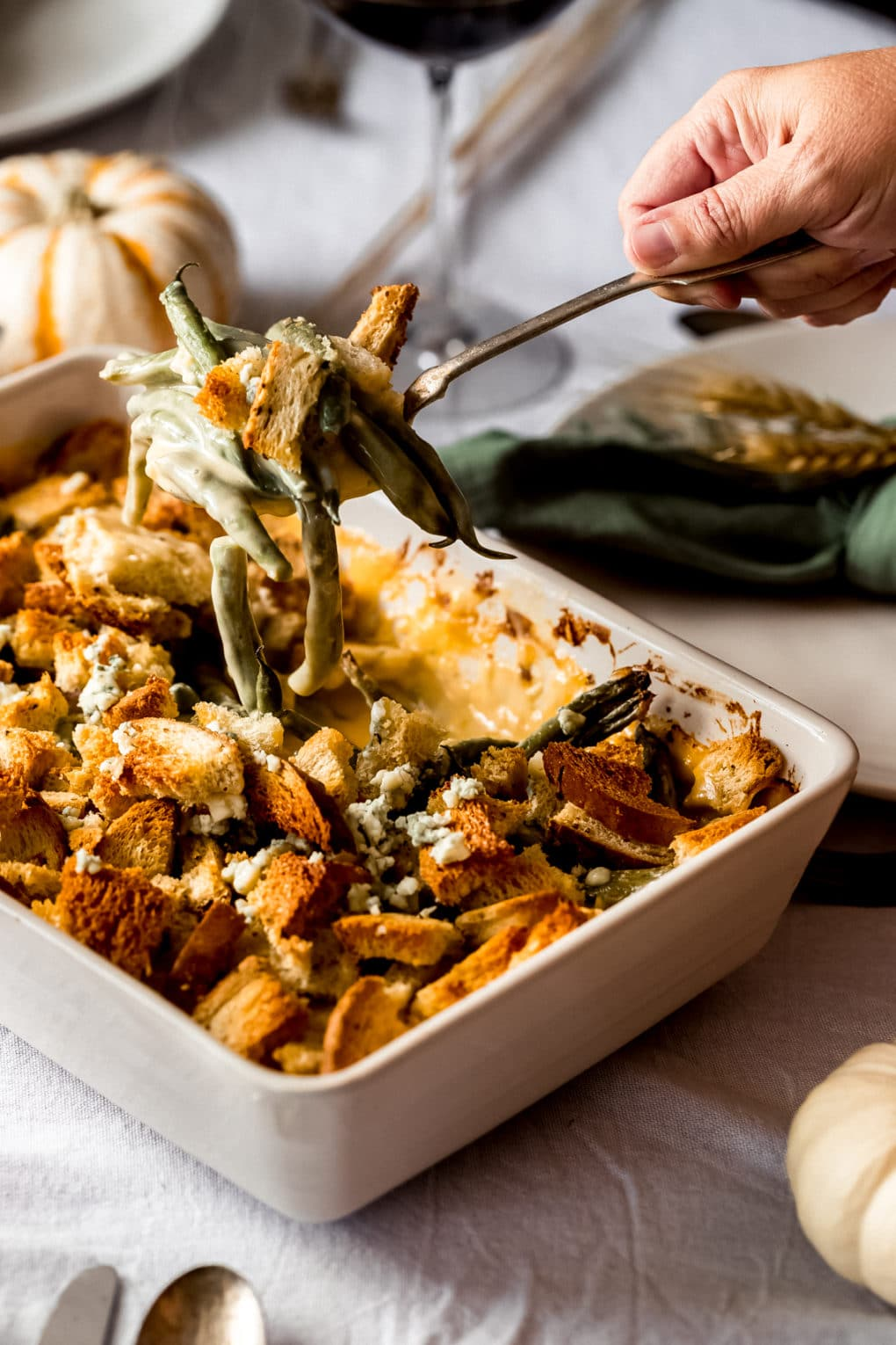 a woman serving up a spoonful of cheesy green bean casserole