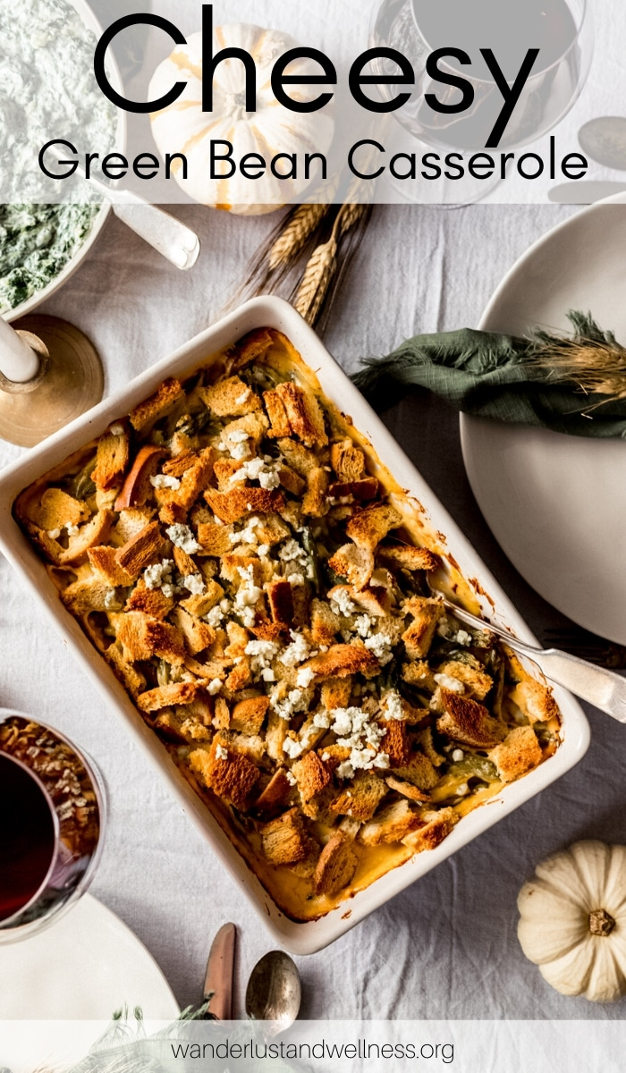 a 9x13 casserole dish with cheesy green bean casserole sitting on a Thanksgiving tablescene