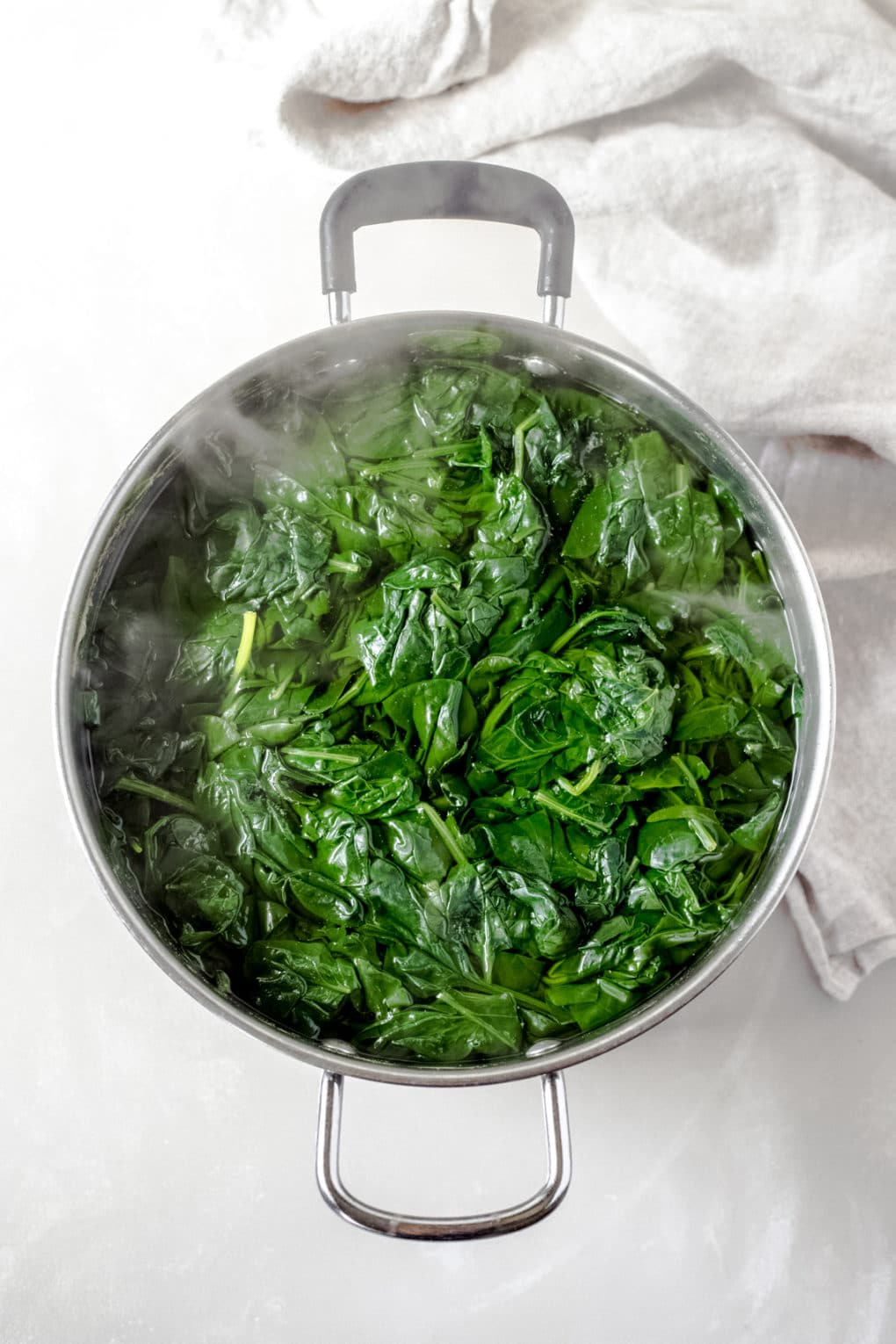 a stock pot of spinach boiling