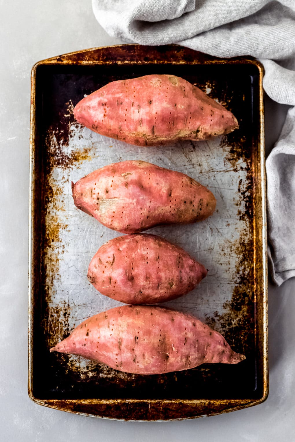 four unbaked sweet potatoes on a baking sheet