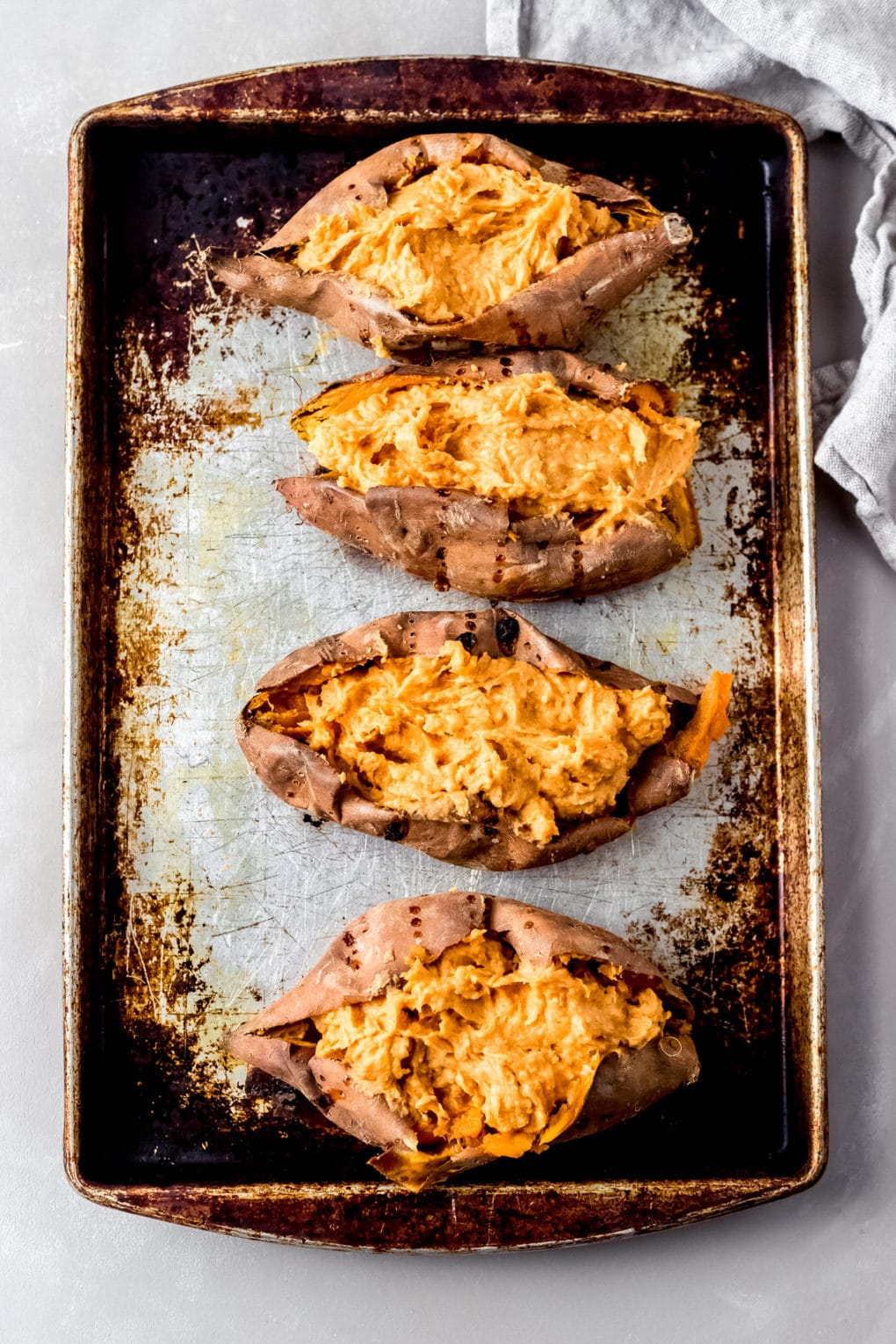 four twice-baked sweet potatoes on a baking sheet