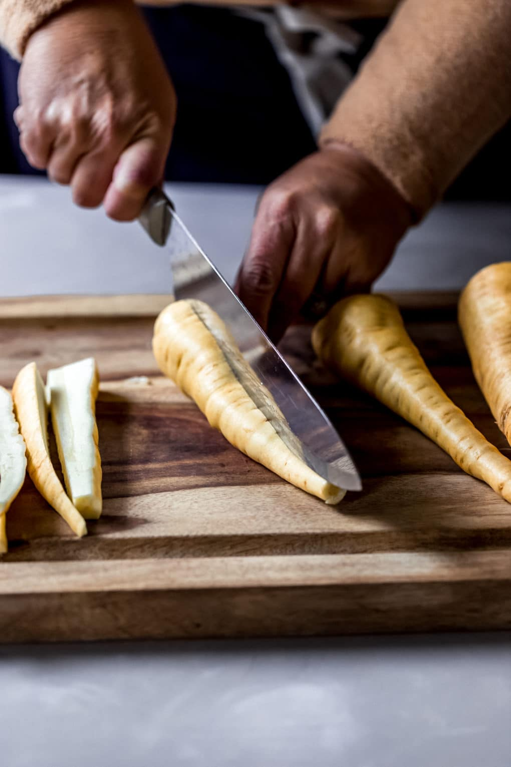 a woman slicing fresh parsnips on a cutting board