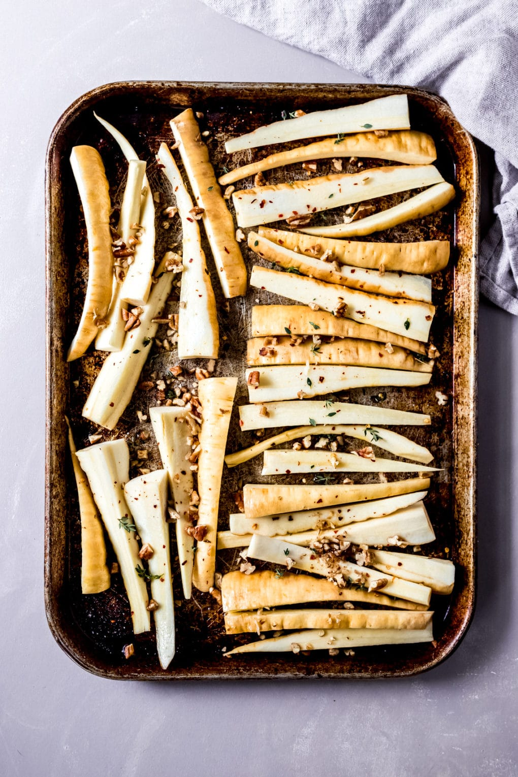 uncooked cut parsnips on a baking sheet ready to roast