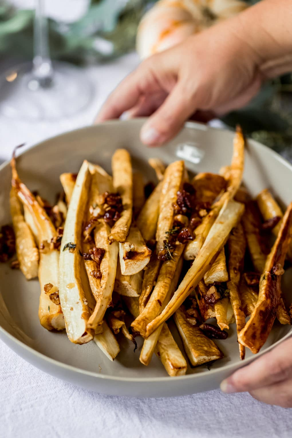 a woman serving a dish of maple roasted parsnips onto a thanksgiving tablescene