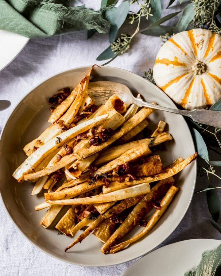 a bowl of maple roasted parsnips on a thanksgiving tablescene
