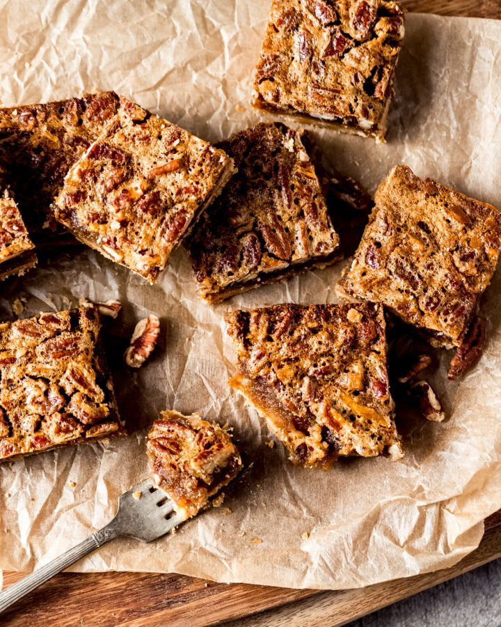 several pecan pie bars stacked on a sheet of parchment paper