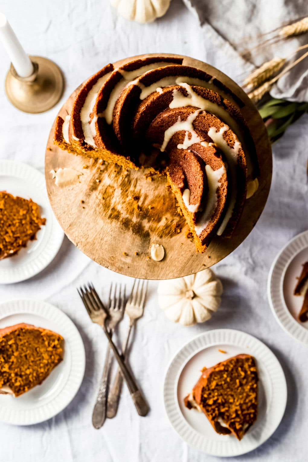 an overhead shot of a pumpkin olive oil cake on a wooden cake stand with four slices cut out that are plated on small white plates