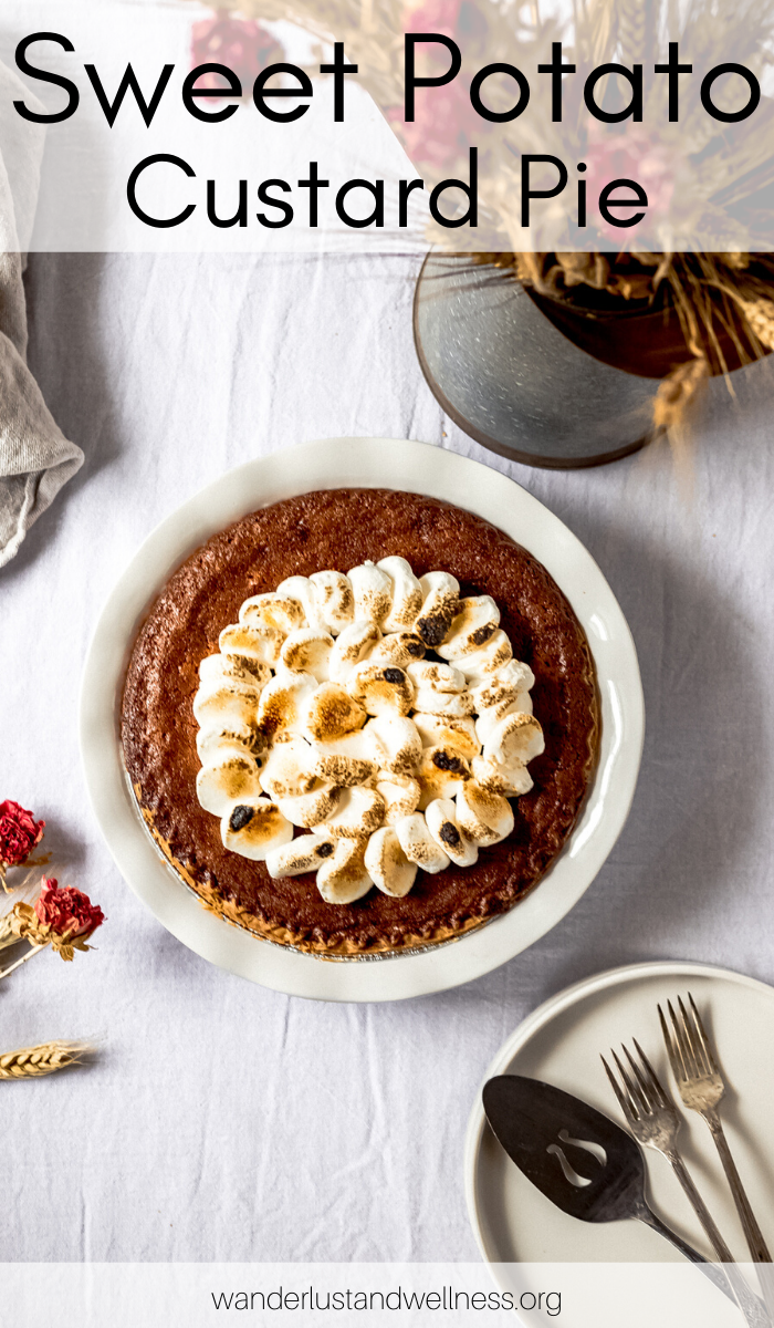 a sweet potato custard pie in a white pie plate with toasted marshmallows on top