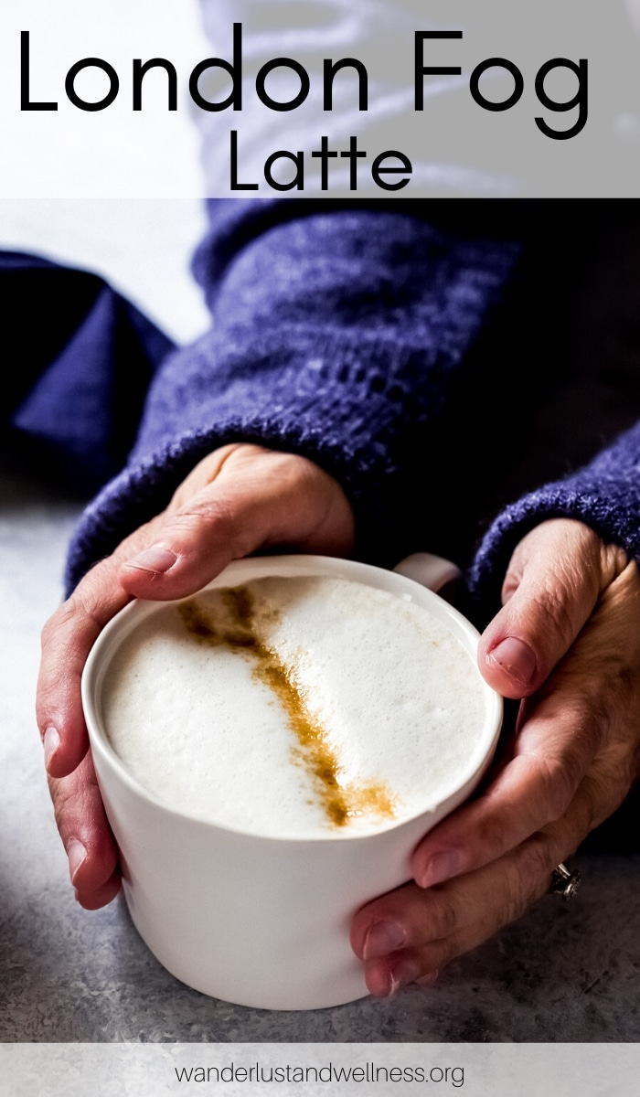 a woman in a blue sweater with hands around a mug of London Fog latte