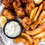 a basket of air fried Mahi Mahi fish & chips with lemon dill aioli