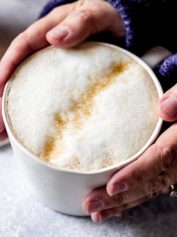 a woman wearing a blue sweater with her hands around a mug of London Fog