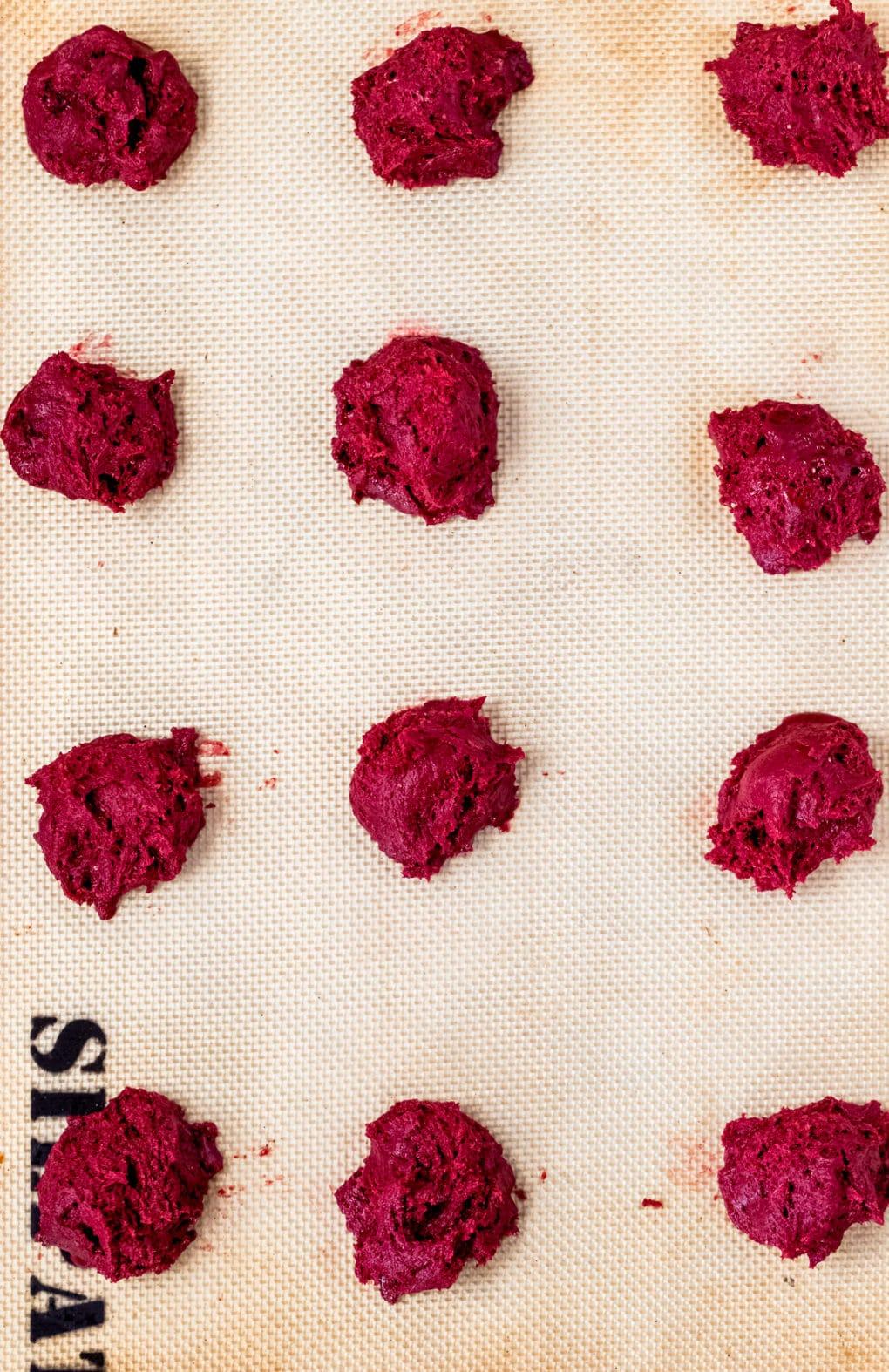 balls of red velvet whoopie pie dough on a silpat-lined baking sheet